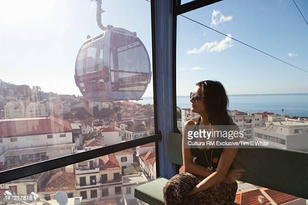 Woman riding gondola over village