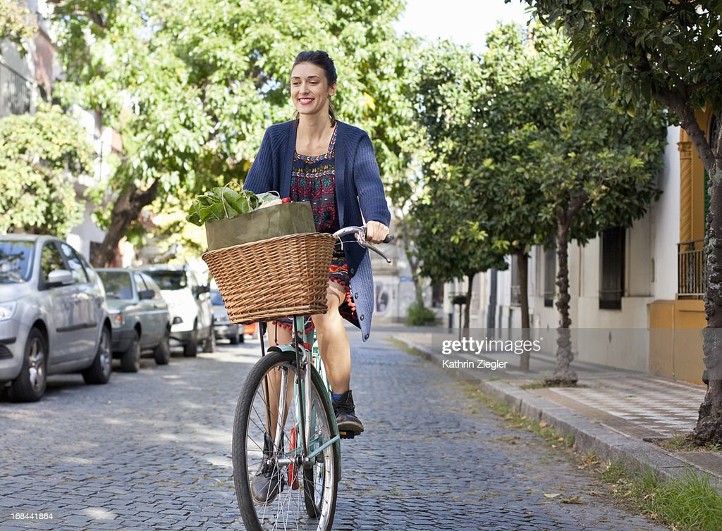 woman riding her bicycle on cobblestone street : Stock Photo