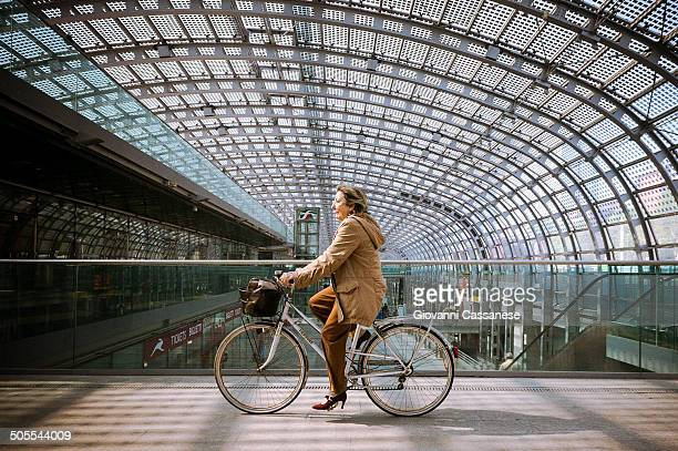 CONTENT] A woman riding her bicycle through an ultra modern architecture Turin Porta Susa Train Station
