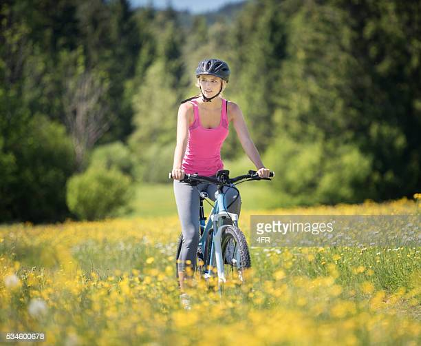 Mujer montando su Mountainbike en un sendero, los campos de flores