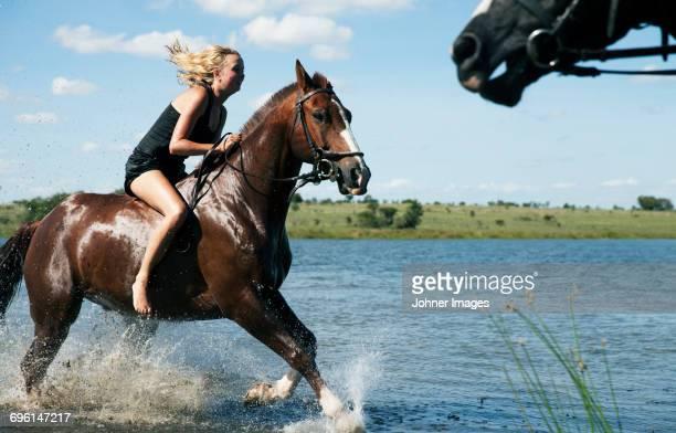 Woman riding horse across river