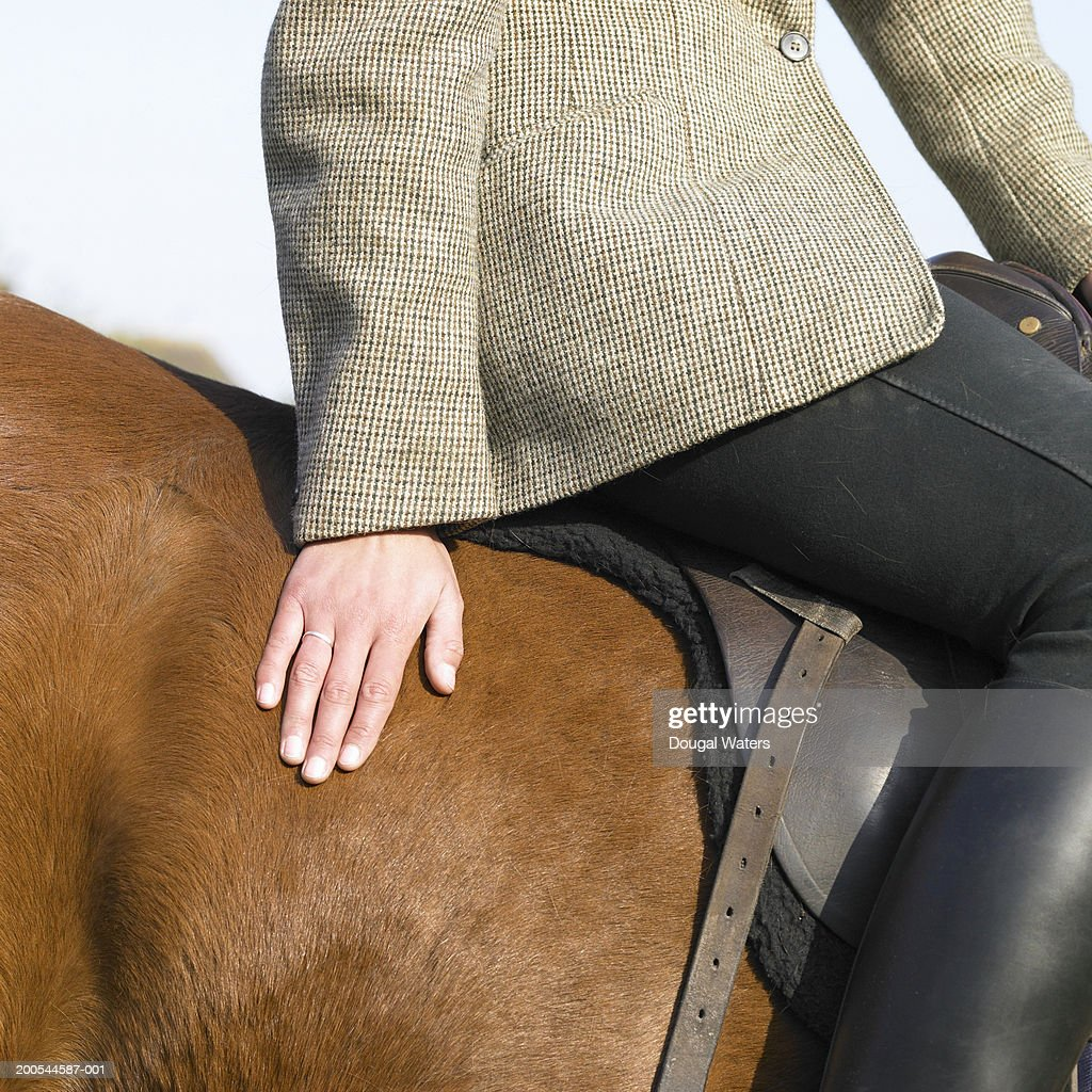 Woman riding horse, close-up, mid section : Stock Photo