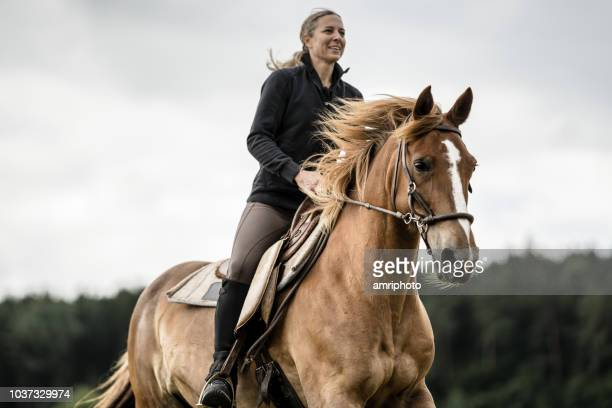 woman riding horse dramatic sky - andare a cavallo foto e immagini stock