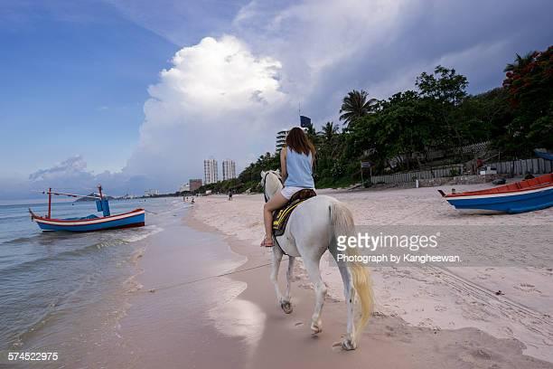 Woman riding horse in beach