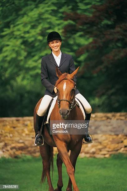 woman riding horse in equestrian attire - cavallo equino foto e immagini stock