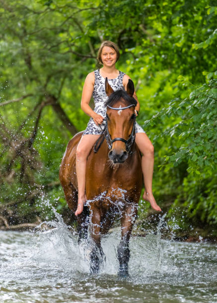 Woman riding horse in Rems river at forest