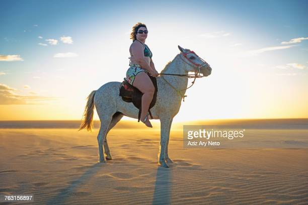 woman riding horse on beach, side view, jericoacoara, ceara, brazil, south america - fat woman at beach stock pictures, royalty-free photos & images
