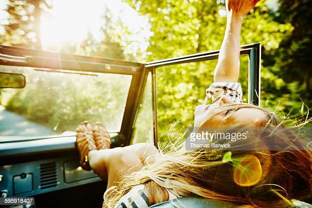 woman riding in passenger seat of convertible - espontânea imagens e fotografias de stock