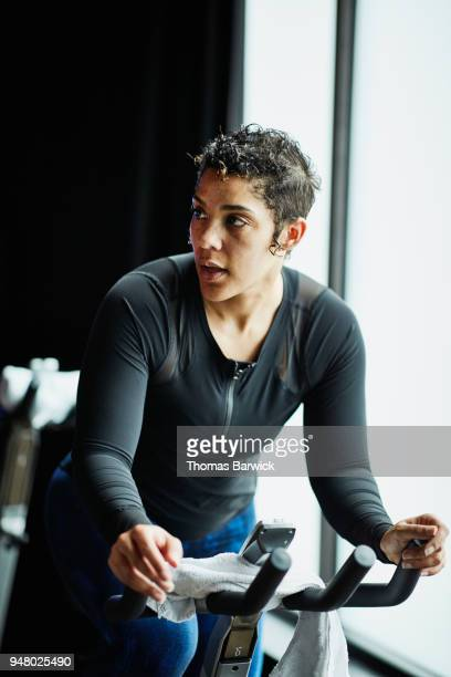 Woman riding indoor bike during class in cycling studio