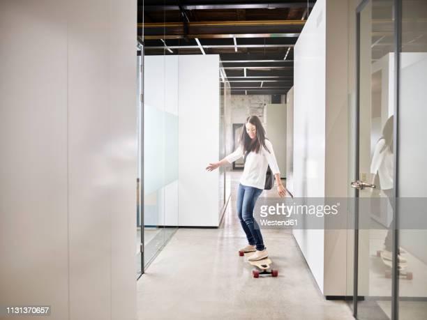 woman riding longboard on office floor - longboard skating stock-fotos und bilder