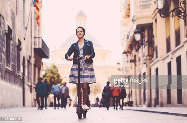 woman riding motor scooter in spain - electric scooter stock pictures, royalty-free photos & images