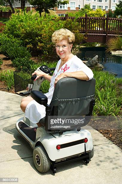 woman riding motor scooter on sidewalk - mobility scooter stock photos and pictures
