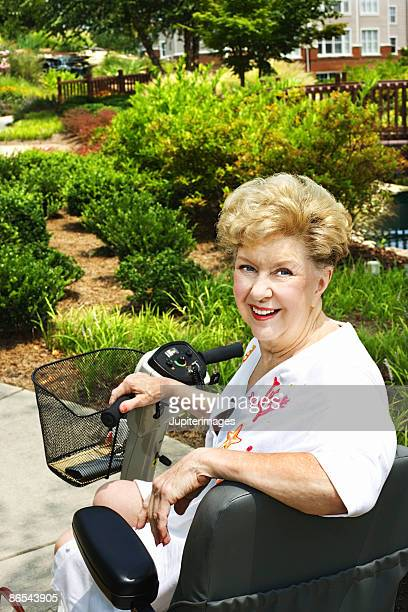 woman riding motor scooter - mobility scooter stock photos and pictures
