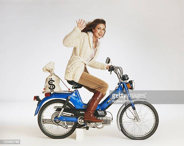 Woman riding motorbike with money bag