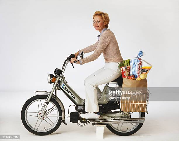Woman riding motorbike with shopping bag