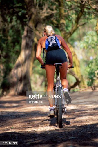 Dirt Bike Images >> Woman Riding Mountain Bike On Dirt Road High-Res Stock Photo - Getty Images