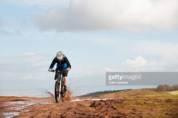 Woman riding mountain bike through mud