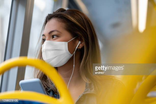 woman riding on a bus wearing a facemask and listening to music with headphones - travel stock pictures, royalty-free photos & images