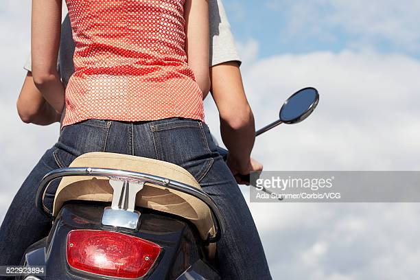 woman riding on back of boyfriend's scooter - low section stock pictures, royalty-free photos & images
