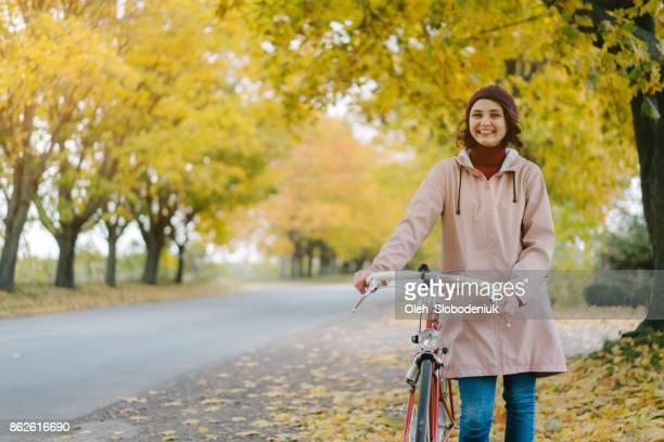 Frau reitet auf dem Fahrrad im Herbst