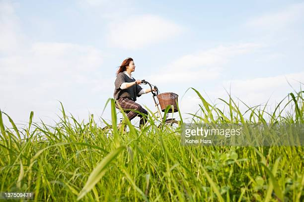 woman riding on bicycle in the grass