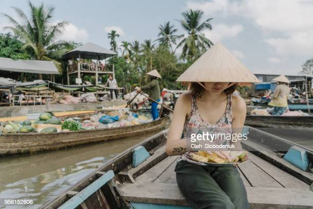 woman riding on boat and eating pineapple  through mekong delta and floating market - hot women on boats stock pictures, royalty-free photos & images