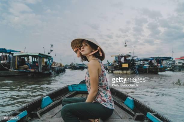 femme à cheval sur le bateau dans le delta du mékong et marché flottant - chapeau chinois photos et images de collection