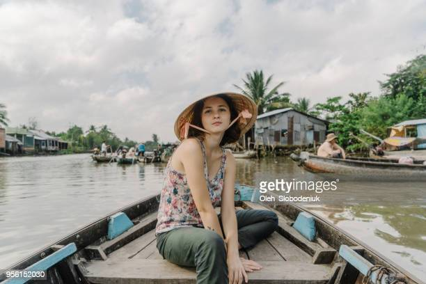 Woman riding on boat through Mekong delta and floating market
