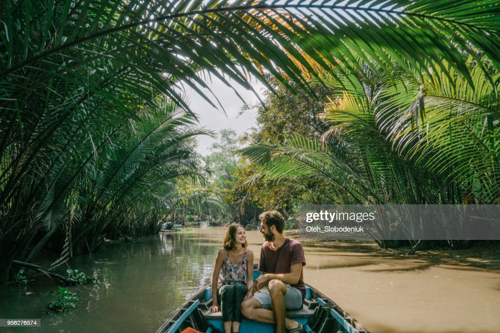 Woman riding on boat through Mekong delta and floating market : Stock Photo