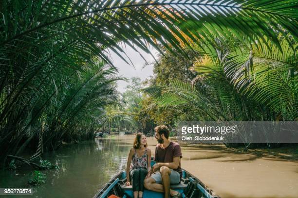 woman riding on boat through mekong delta and floating market - vietnam imagens e fotografias de stock