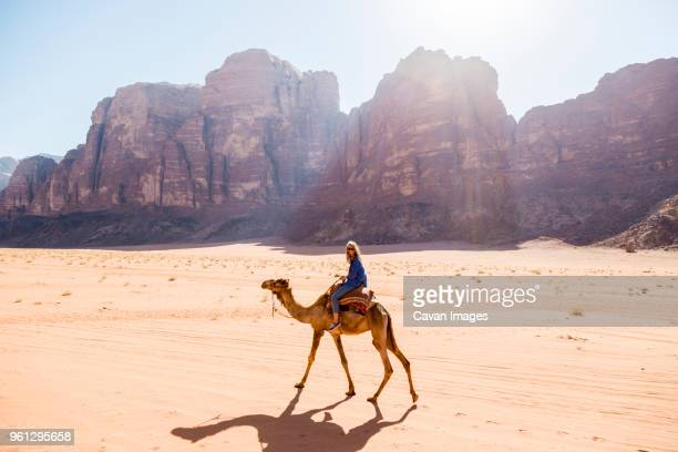 woman riding on camel in desert - camel stock pictures, royalty-free photos & images
