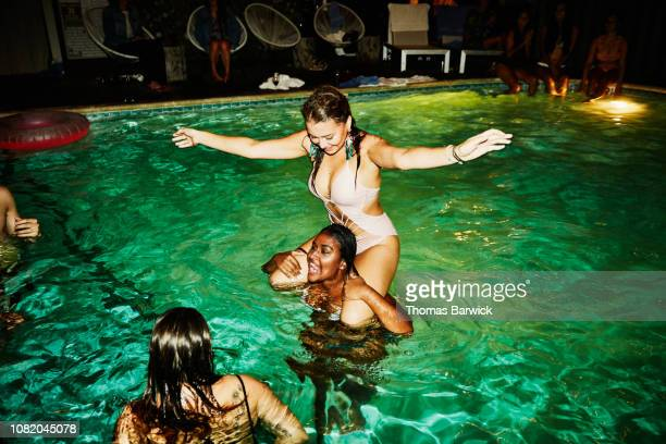 woman riding on friends shoulders during party in hotel pool - naughty america stock pictures, royalty-free photos & images