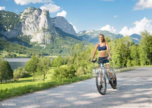 Mujer cabalgando sobre su Mountainbike, lago Grundlsee, de Alpes austríacos