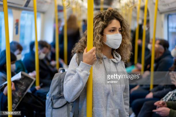 woman riding on the metro wearing a facemask to avoid an infectious disease - public transport stock pictures, royalty-free photos & images