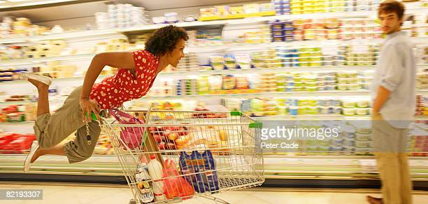 Woman riding on trolly in supermarket