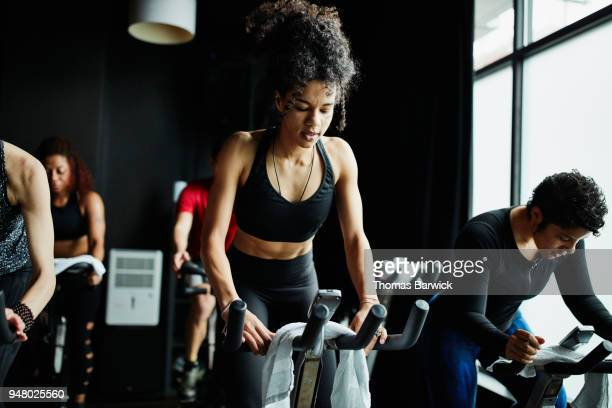 woman riding out of saddle during indoor cycling class in fitness studio - peloton stock pictures, royalty-free photos & images