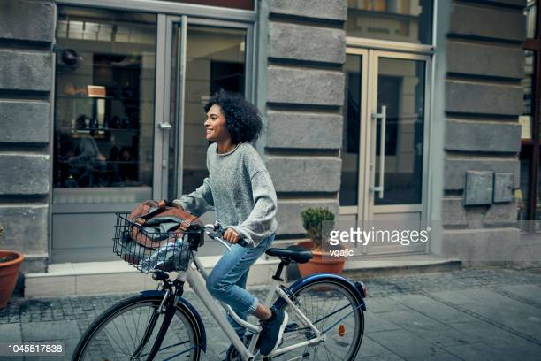 woman riding rented bicycle in a city - bicycle stock pictures, royalty-free photos & images