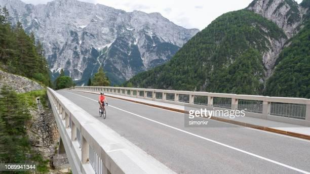 橋の上の女性乗馬道のバイク - 自転車ロードレース ストックフォトと画像