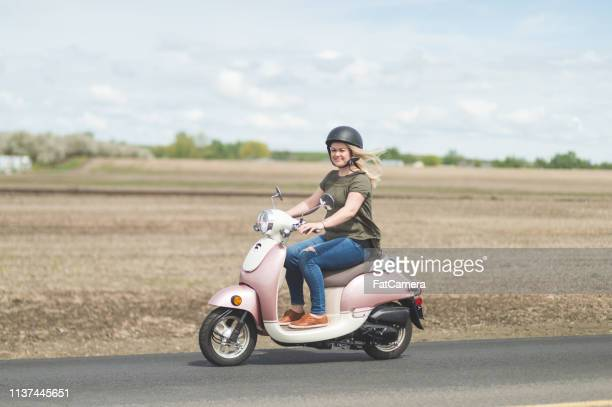 scooter da equitação da mulher no país - moped - fotografias e filmes do acervo