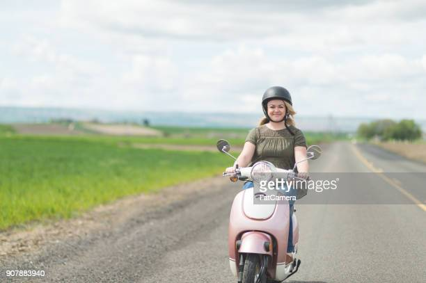 woman riding scooter in country - moped stock photos and pictures