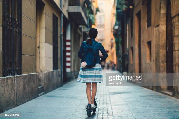 woman riding scooter on her way to work - alternative fuel vehicle stock pictures, royalty-free photos & images