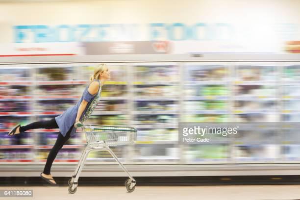 Woman riding shopping trolley down aisle