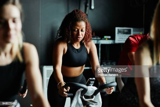 woman riding stationary bike during fitness class in cycling studio - peloton stock pictures, royalty-free photos & images