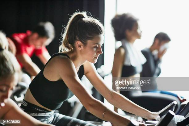Woman riding stationary bike during indoor cycling class in fitness studio