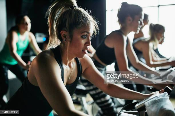 Woman riding stationary bike during indoor cycling class
