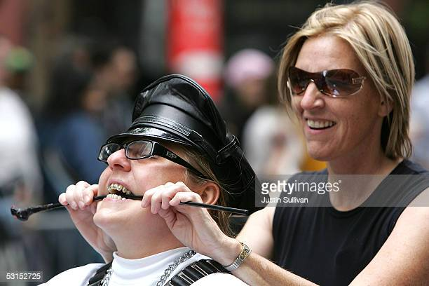 """Woman riding with the group """"Dykes on Bikes"""" bites down on a whip during the 2005 San Francisco Pride Parade June 26, 2005 in San Francisco,..."""