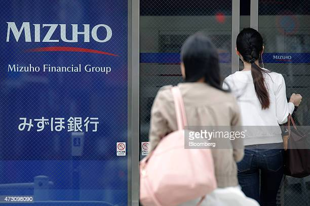 A woman right enters a Mizuho Bank Ltd branch in Tokyo Japan on Tuesday May 12 2015 Mizuho Financial Group Inc is scheduled to release their fullyear...