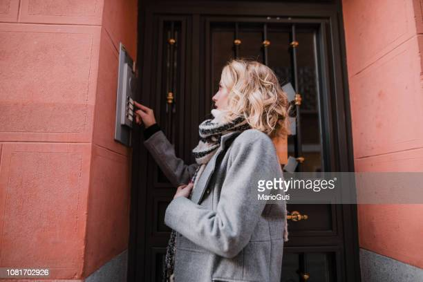 woman ringing an apartment bell - intercom stock pictures, royalty-free photos & images