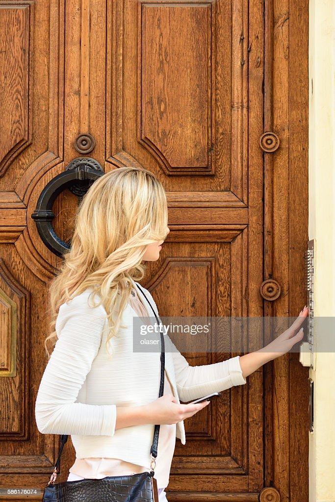 Woman Ringing Door Bell Apartment Building Stock Photo