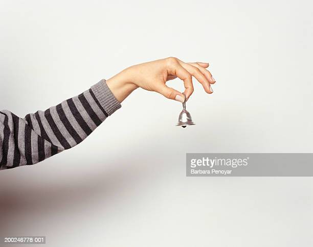 woman ringing little bell, close-up of hand - long sleeved stock pictures, royalty-free photos & images